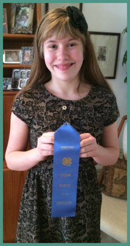 At home with her blue ribbon. Nervous at first, she came home so proud of accomplishment.