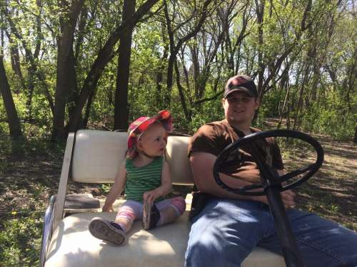 Home is where a golf cart ride is always waiting for you.  Ava and Uncle Marshall in NoDak!