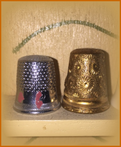 The thimble on the left is from my mom - it has her nail polish on it from when she was in high school home ec. class in the 50's! The one on the left we picked up in the 70's in New Braunfels, TX at a German restaurant/gift shop.