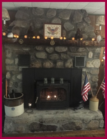 Pine cone string lights, vintage Americana and flags, and candlelight make my friend's lake house fireplace summer cozy.