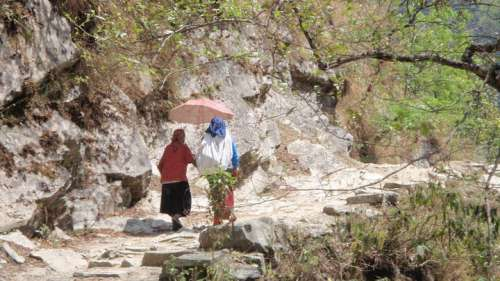 An elderly woman and a younger woman trekking between villages.