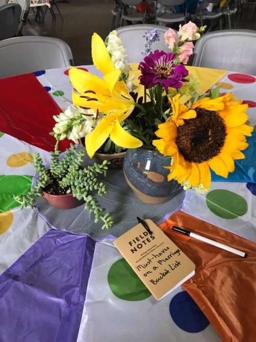 "The table decor: Parachute table cloth, farmers market flowers in hand thrown vases, succulents in hand thrown pots and a ""guest book"" at each table."
