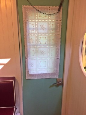 We needed privacy but didn't want to drill holes. I could not find fabric to match the curtains, so I found this vinyl paneled 'fabric' and cut it to fit, using Gorilla tape to hang. The whole thing cost me $5.00, and I think it goes well with the curtains.