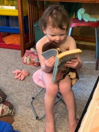 Opal reading a Little House book to her stuffed animals.