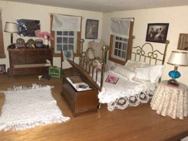 "The master bedroom was fun to set up. I knitted the rug and bedding using size ""1"" needles."