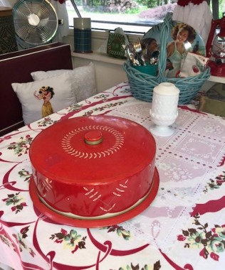 A vintage cake tin sits on the table. The hula girl pillow was made by me from a vintage dishtowel.