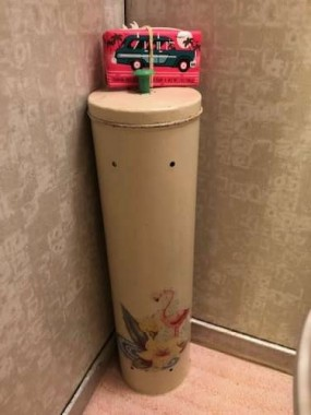 A vintage toleware toilet paper holder inspired the bathroom's flamingo theme.