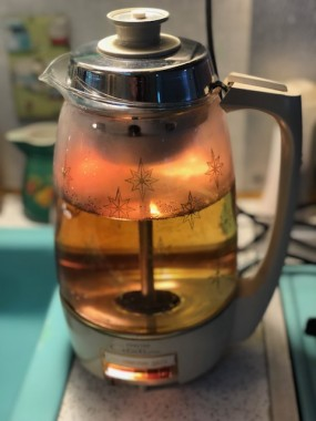 """At last year's rally, I was smitten by another camper's light-up vintage coffee maker. I love the """"atomic starburst"""" pattern of mine, matching the camper's all-original laminate countertop. From the 60's, it still makes piping hot coffee. If you buy one online, ask the seller if it perks coffee, not just if it """"works"""". Two lights should go on while perking, one should go off when the coffee is ready."""