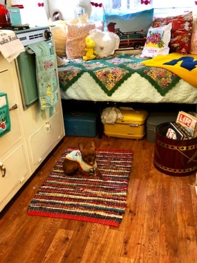 "Vintage linens and lots of throw pillows make a comfy spot. A pristine 60s portable grill, too cute to use for its use, is repurposed as a magazine/book rack. A vintage tool box holds tools, while vintage luggage makes for storage and cute decor. All is ""Pipsqueak"" approved."