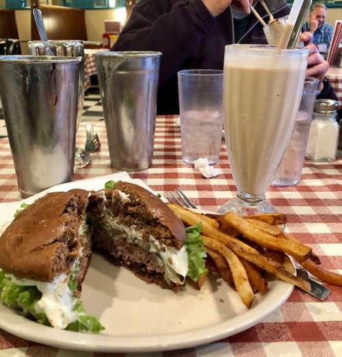 I am definitely not a food stylist...this is a plaza burger from convention grill in Minneapolis--it has sour cream and diced onions on a rye bun.  Inspired by a restaurant in my college town! Paired with a chocolate malt and fries.  American as it gets.