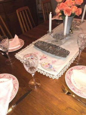 Vintage pink and red dishes, and vintage linens set the table for Easter