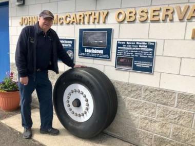 Bob Lambert stands in front of a space shuttle landing tire
