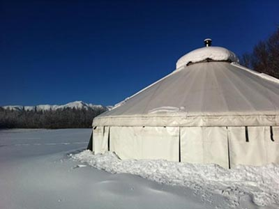 A snow-covered yurt, with Fields in the background
